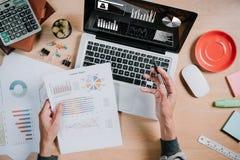 Бизнесмен анализируя диаграммы вклада с портативным компьютером на таблице стола офиса Стоковые Фото