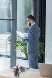 Бизнесмен анализируя документы пока стоящ на окне в офисе Стоковые Фото