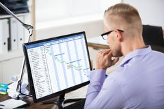 Бизнесмен анализируя планово-контрольный график на компьютере стоковое изображение