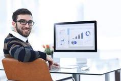 Бизнесмен анализируя финансовые диаграммы на компьютере Стоковые Фото