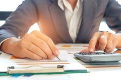 Бизнесмен анализирует данные по диаграммы и использует калькулятор к calcul Стоковое Изображение