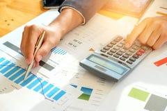 Бизнесмен анализирует данные по диаграммы и использует калькулятор к calcul Стоковая Фотография