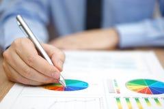 Бизнесмен анализирует бизнес-отчет с диаграммами и диаграммой Стоковые Фотографии RF