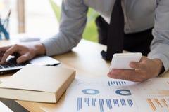 Бизнесмен анализируя диаграммы и диаграммы с smartphone и comp Стоковые Изображения RF
