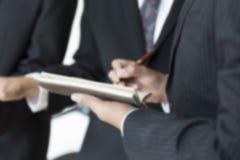 Бизнесмен анализируя и обсуждая с нерезкостью ручки и тетради Стоковое Фото