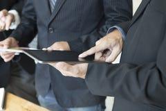 Бизнесмен анализируя и обсуждая с таблеткой и документом Стоковые Фото