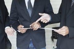 Бизнесмен анализируя и обсуждая с таблеткой и документом Стоковое Изображение RF