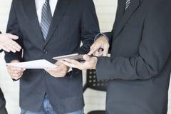 Бизнесмен анализируя и обсуждая с таблеткой и документом Стоковое Фото