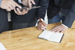 Бизнесмен анализируя и обсуждая с таблеткой и тетрадью Стоковое фото RF