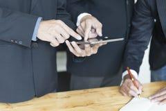 Бизнесмен анализируя и обсуждая с таблеткой и тетрадью Стоковые Изображения