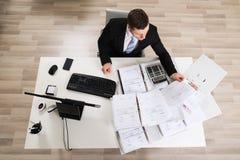 Бизнесмен анализируя документы на столе компьютера Стоковое Фото