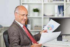 Бизнесмен анализируя документы на столе офиса Стоковые Фотографии RF