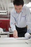 Бизнесмен анализируя проект архитектора в офисе Стоковые Фотографии RF