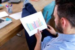 Бизнесмен анализируя растущие диаграммы на его столе Стоковые Изображения RF