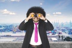 Бизнесмен Афро с бинокулярным на промышленном порте Стоковое Изображение