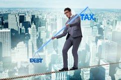 Бизнесмен балансируя между задолженностью и налогом стоковая фотография