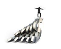 Бизнесмен балансируя на домино денег доллара Стоковая Фотография