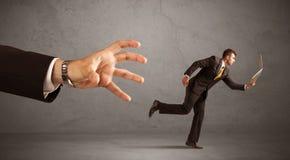 Бизнесмен бежать от руки Стоковое Фото