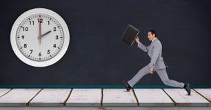 Бизнесмен бежать поздно с часами установил на стене Стоковое Изображение