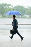 Бизнесмен бежать с зонтиком Стоковое Фото
