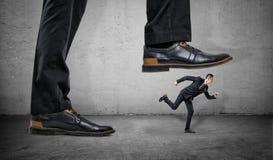 Бизнесмен бежит далеко от большой ноги на серой конкретной предпосылке Стоковая Фотография RF
