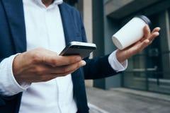 Бизнесмен, бизнесмен с телефоном, бизнесмен держа кофе Стоковое фото RF