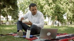 Бизнесмен битника выпивая чашку кофе в кафе города во время времени обеда Он работает на компьтер-книжке и вызывает мимо видеоматериал