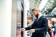 Бизнесмен битника покупая билет в машине на станции метро стоковые изображения
