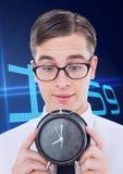 Бизнесмен болвана держа часы против предпосылки с часами Стоковые Изображения