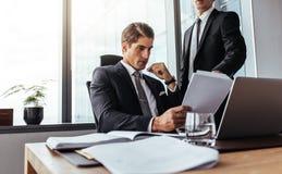 Бизнесмен будет партнером читать некоторую обработку документов стоковое фото rf