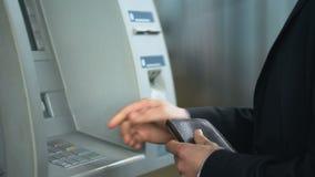 Бизнесмен вводя кредитную карточку в ATM, входя в код штыря для того чтобы получить деньги сток-видео