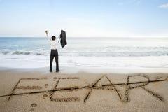 Бизнесмен веселя с словом страха уничтожил линию на пляже песка Стоковая Фотография RF