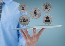 Бизнесмен взаимодействуя с людьми в графиках cogs против голубой предпосылки Стоковое Фото