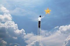 Бизнесмен взбирается вверх на лестнице для достижения концепции звезды, успешных и выигрыша стоковое фото rf