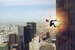 Бизнесмен взбирается здание с веревочкой Концепция определения стоковое фото rf