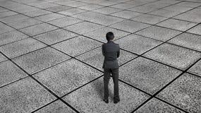 Бизнесмен вид сзади думая и стоя на бесконечном крыть черепицей черепицей flo Стоковые Фото