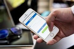 Бизнесмен вносит в журнал дальше к Facebook на его телефоне стоковое изображение