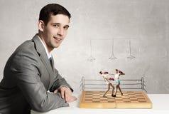 Бизнесмен воюя на доске стоковое фото