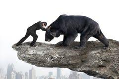 Бизнесмен воюя против черного медведя на скале с citysc неба Стоковые Фото