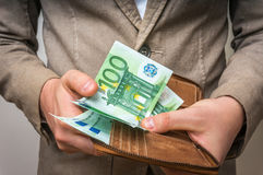 Бизнесмен вручает держать бумажник с стогом денег Стоковые Фотографии RF