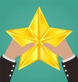 Бизнесмен вручает заразительную звезду золота Стоковая Фотография