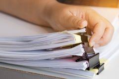 Бизнесмен вручает искать незаконченные стога документов бумаги Стоковое Фото
