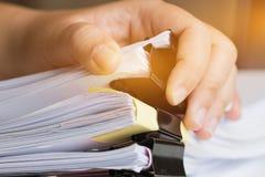 Бизнесмен вручает искать незаконченные стога документов бумаги Стоковое фото RF