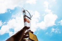 Бизнесмен вручает поднятый и держащ светлое tropy, покажите successfu Стоковая Фотография