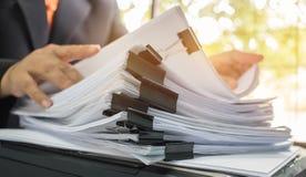 Бизнесмен вручает работу в стогах бумажных файлов для искать Стоковые Изображения