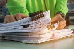 Бизнесмен вручает работу в стогах бумажных файлов для искать Стоковые Фото
