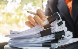 Бизнесмен вручает работу в стогах бумажных файлов для искать Стоковые Изображения RF
