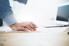 Бизнесмен вручая карандаш и работая компьтер-книжка новый проект дела Родовая тетрадь дизайна на таблице запачканный Стоковые Фотографии RF