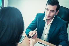 Бизнесмен вручая ручку к женщине для подписания контракта Стоковые Изображения RF
