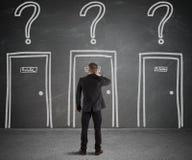 Бизнесмен выбирая правую дверь стоковые изображения